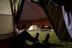 Tourist lying in tent with a view of camping Stock Image