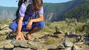 Tourist machen eine Pyramide von den Steinen stock footage