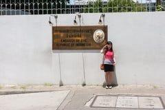 Tourist macht ein Foto mit Botschaftszeichen lizenzfreies stockbild