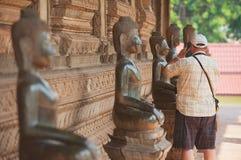 Tourist macht Foto von der Buddha-Statue außerhalb Tempels Hor Phra Keo in Vientiane, Laos Stockbilder