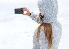 Tourist macht selfies auf einem hohen Bergabhang lizenzfreie stockfotografie