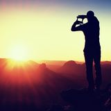Tourist make frame with palms and fingers on both hands. Hiker on rocky cliff, daybreak in rocky mountains. Stock Photo