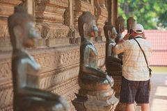 Tourist makes photo of the Buddha statue outside of Hor Phra Keo temple in Vientiane, Laos. Stock Images