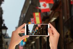 Tourist makes a photo of flags of various world countries. A tourist is taking a photo of flags of various world countries on a mobile phone stock photos