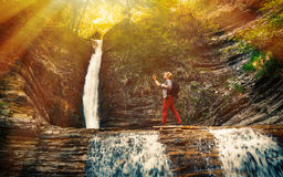 The tourist makes a self-portrait against the backdrop of a landmark waterfall. Male traveler makes a self-portrait against the backdrop of a landmark waterfall Stock Photos