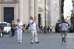 Tourist makes a video of large soap bubbles. A couple of tourists strolling in the historic center of Rome (Italy). The husband makes a video of some large soap Royalty Free Stock Images
