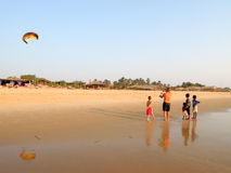 Tourist making fly a kite on the beach of Candolim Royalty Free Stock Images