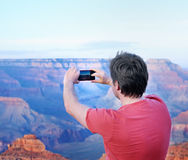 Tourist making mobile photo of the famous Grand Canyon. Middle age male tourist making mobile photo of the famous Grand Canyon from Mather Point Royalty Free Stock Photos