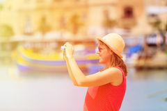 Tourist making photo of colorful traditional boats in Malta Stock Photo
