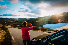 Tourist making photo of nature while travel by car in mountains at sunset. Tourist making photo of nature while travel by car in snow mountains at sunset stock photo