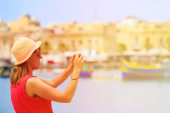 Tourist making photo of traditional boats in Malta Royalty Free Stock Photo