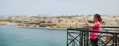 Tourist making photo of Valetta, Malta, travel concept stock photography