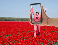Tourist making photo of womanin tulip field Royalty Free Stock Photography