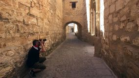 Tourist making photos in, medieval neighborhood, alleyway with stone arch, Baeza, Patrimony of the Humanity, Andalu. Tourist making photos in, medieval stock video