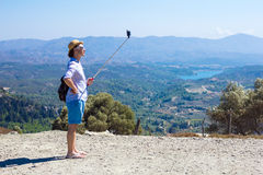 Tourist making selfie against the background of beautiful scenery Royalty Free Stock Images