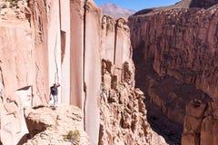 Tourist man adventurer backpacker standing above deep canyon, Bolivia. Explorer traveler adventurer man tourist backpacker standing above deep desert canyon Stock Photography