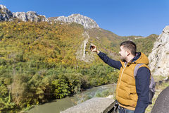 Tourist man in the autumn mountain taking photos with the phone Royalty Free Stock Images