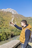 Tourist man in the autumn mountain taking photos with the phone Royalty Free Stock Photography