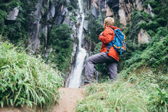 Tourist man with backback rest near the waterfall in rainy fores Royalty Free Stock Image
