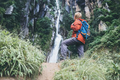 Tourist man with backback rest near the waterfall in rainy fores Royalty Free Stock Photo