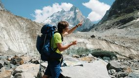 Tourist man with a backpack exploring the route on the map and phone GPS, adds a map and goes on a route in the mountain. Hike stock image