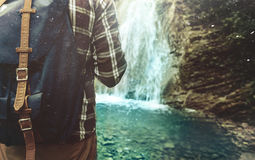 Tourist Man With Backpack Reached His And Stands On Waterfall Background Closeup Hiking Journey Travel Trek Concept. Man Traveler with A Backpack Stands With His royalty free stock photo