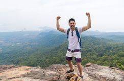 Tourist Man With Backpack Standing On Mountain Top Raised Hands Happy Smiling Over Beautiful Landscape. Young Guy On Hike Royalty Free Stock Photography