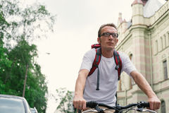 Tourist man on a bike at city street Royalty Free Stock Image