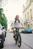 Tourist man on a bike at city street Royalty Free Stock Photography