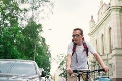 Tourist man on a bike at city street Royalty Free Stock Photos