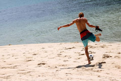 Tourist man with cameras playing football on the beach. Tourist man with cameras playing football on the beach,Samui island Thailand.July 5,2017 Royalty Free Stock Photos