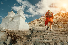 Tourist man climbs up stairs to tibetan holy place in Himalaya m Stock Photos