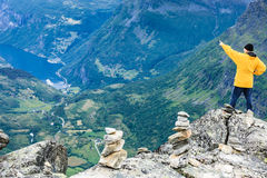 Tourist man on Dalsnibba viewpoint Norway. Tourism vacation and travel. Male tourist enjoying Geirangerfjord and mountains landscape from Dalsnibba viewpoint Stock Images