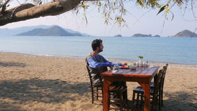 Tourist man eating gorgeous breakfast beach with majestic sea background stock video footage