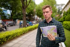 Tourist man exploring Ho Chi Minh city in Vietnam and holding map. Portrait of young handsome tourist man exploring Ho Chi Minh city in Vietnam stock photography