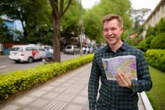 Tourist man exploring Ho Chi Minh city in Vietnam and holding map. Portrait of young handsome tourist man exploring Ho Chi Minh city in Vietnam stock photo