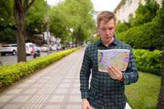 Tourist man exploring Ho Chi Minh city in Vietnam and holding map. Portrait of young handsome tourist man exploring Ho Chi Minh city in Vietnam royalty free stock photography