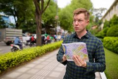Tourist man exploring Ho Chi Minh city in Vietnam and holding map. Portrait of young handsome tourist man exploring Ho Chi Minh city in Vietnam royalty free stock image