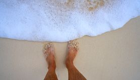 Tourist feet in tropical white sand beach. Tourist man feet in tropical white sand beach vacation concept Royalty Free Stock Photography