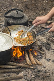 Tourist man fry food in a pan on the campfire Royalty Free Stock Image