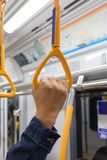 Tourist man hand holding a handrails of train. In subway Stock Photo