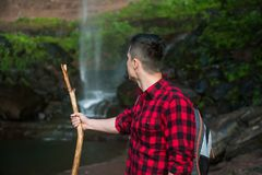 Tourist man hiking in mountains with scenic waterfall view at summer time. Royalty Free Stock Image