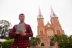 Tourist man holding map in front of Notre Dame Cathedral in Ho Chi Minh City. Portrait of young handsome tourist man exploring Ho Chi Minh city in Vietnam stock image