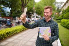Tourist man holding map and taking selfie with mobile phone. Portrait of young handsome tourist man exploring Ho Chi Minh city in Vietnam stock photo