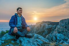 Free Tourist Man In A Blue Jacket Sits On A Rock High In The Mountains, Above The Clouds And Enjoys The Sunset Copy Space. The Concept Stock Photos - 185304003