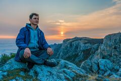 Free Tourist Man In A Blue Jacket Sits On A Rock High In The Mountains, Above The Clouds And Enjoys The Sunset Copy Space. The Concept Stock Images - 185390724