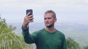 Tourist man making selfie photo by mobile phone on panoramic view from mountain peak. Travel blogger posing for mobile.  stock footage