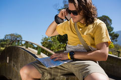 Tourist man with map talking on mobile phone Royalty Free Stock Photo