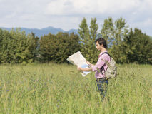 Tourist man mountain. Man tourist on a trip reading a map for the best way Royalty Free Stock Photos