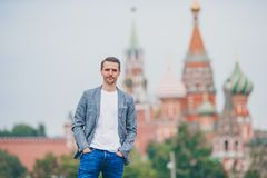 Happy young urban man in european city. Tourist man outdoors on background of Kremlin and St Basils Church. Portrait of businessman in big city royalty free stock image